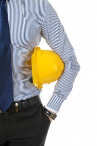 Businessman with construction yellow helmet. Isolated on white